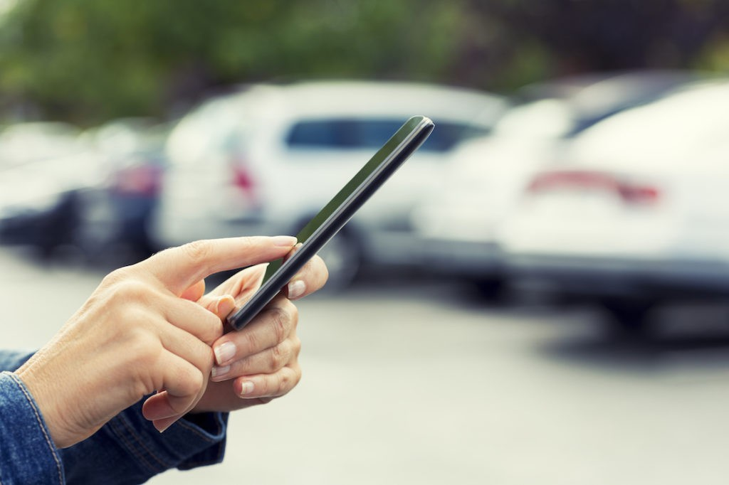 Female's hand looking for her car with smartphone API in a parking lot. Blur Cars background.